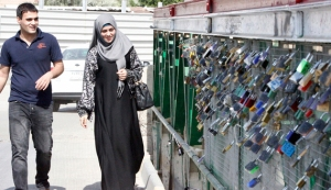 A couple walks on a bridge covered with padlocks hung by lovers in Basra