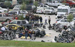 FILE - In this May 17, 2015 file photo, authorities investigate a shooting in the parking lot of the Twin Peaks restaurant, in Waco, Texas. Bikers and public watchdogs have criticized authorities here for how they've handled the shooting investigation, citing the mass arrests of more than 170 people held for days or weeks on $1 million bonds without sufficient evidence to support those arrests four months after the shootings. No formal charges have been made, and it remains unclear whose bullets, including police bullets, struck the dead and injured, or when cases will be presented to a grand jury, which is currently led by a Waco police detective.  (AP Photo/Jerry Larson, File)